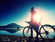Silhouette de sportif tenant la bicyclette sur la plage de lac, ciel nuageux de coucher du soleil coloré à l'arrière-plan Images stock