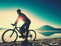 Silhouette de sportif tenant la bicyclette sur la plage de lac, ciel nuageux de coucher du soleil coloré à l'arrière-plan Photos libres de droits