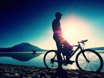 Silhouette de sportif tenant la bicyclette sur la plage de lac, ciel nuageux de coucher du soleil coloré à l'arrière-plan Image stock