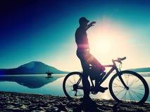 Silhouette de sportif tenant la bicyclette sur la plage de lac, ciel nuageux de coucher du soleil coloré à l'arrière-plan Photographie stock libre de droits