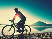 Silhouette de sportif tenant la bicyclette sur la plage de lac, ciel nuageux de coucher du soleil coloré à l'arrière-plan Photographie stock