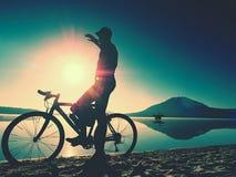 Silhouette de sportif tenant la bicyclette sur la plage de lac, ciel nuageux de coucher du soleil coloré à l'arrière-plan Photos stock