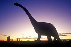 Silhouette de statue du brontosaure, écart-type au coucher du soleil Image libre de droits