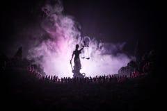 Silhouette de statue géante brouillée de justice de dame avec l'épée et d'échelle se tenant derrière la foule la nuit avec le fon photographie stock libre de droits