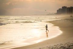 Silhouette de surfer marchant sur la plage pendant le coucher du soleil Photos libres de droits