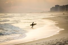 Silhouette de surfer marchant sur la plage pendant le coucher du soleil Photographie stock