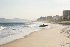 Silhouette de surfer marchant sur la plage pendant le coucher du soleil Images libres de droits