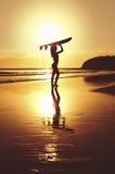 Silhouette de surfer se tenant avec le panneau de ressac sur la plage Photographie stock libre de droits