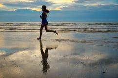 Silhouette de taqueur de femme fonctionnant sur la plage de coucher du soleil avec la réflexion, la forme physique et le sport Image libre de droits