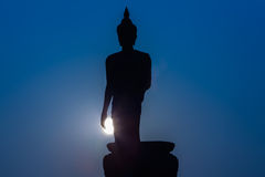 Silhouette de tenir la grande statue de Bouddha pendant le temps crépusculaire image stock
