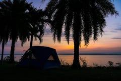 Silhouette de tente pour camper tout près le réservoir à l'aube Photographie stock