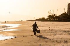 Silhouette de travailleur marchant sur la plage pendant le coucher du soleil Images stock