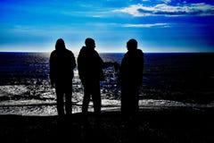 Silhouette de trois drunks par la mer images stock