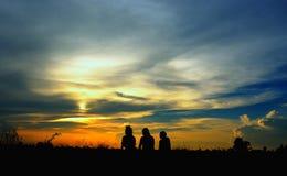 Silhouette de trois filles s'asseyant sur l'herbe au coucher du soleil Photos stock