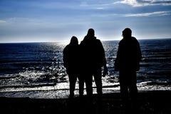 Silhouette de trois hommes par la mer Photo stock
