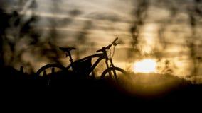 Silhouette de vélo de montagne avec la lumière de coucher du soleil Photographie stock libre de droits