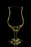 Silhouette de verre de cocktail jaune sur le fond noir Photographie stock libre de droits