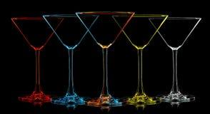 Silhouette de verre multicolore de martini sur le noir Photographie stock libre de droits