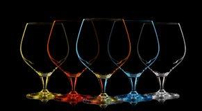 Silhouette de verre multicolore de whiskey sur le noir Photographie stock libre de droits