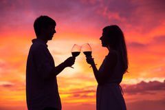 Silhouette de vin potable de couples au coucher du soleil Photo stock