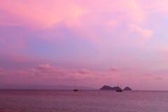 Silhouette de voilier et d'île en mer au coucher du soleil Photo stock
