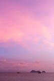 Silhouette de voilier et d'île en mer au coucher du soleil Images stock