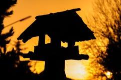 silhouette de volière dans le coucher du soleil Photos stock