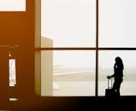 Silhouette de voyageur féminin faisant l'appel téléphonique devant le pont en jet dans la porte de départ du ` s d'aéroport Images stock