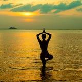 Silhouette de yoga au coucher du soleil Image stock