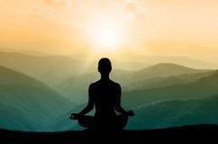 Silhouette de yoga sur la montagne dans les rayons de soleil Photographie stock libre de droits