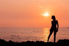 Silhouette debout de femme sur le fond de mer de retour lumineux Photographie stock libre de droits