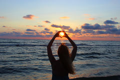 silhouette Den unga härliga flickan korsade hans händer i form av hjärta, som solens strålar gör till och med vägen Fotografering för Bildbyråer