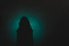 Silhouette of depress woman standing in the dark with light shin Stock Photos