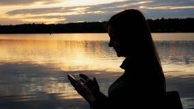 Silhouette der weiblichen Touristen auf dem See bei Sonnenuntergang am Abend, verwenden Sie Smartphone, surfen Internet stock video