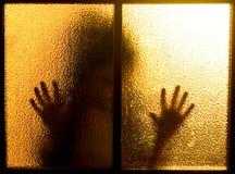 Silhouette derrière une trappe en verre Photographie stock libre de droits