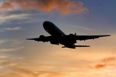 Silhouette des aéronefs au coucher du soleil Photos libres de droits