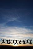 Les adolescents sautant dans le coucher du soleil Photos stock