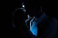 Silhouette des ajouter affectueux à une lumière bleue derrière images stock