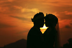 Silhouette des ajouter de mariage au coucher du soleil Images stock