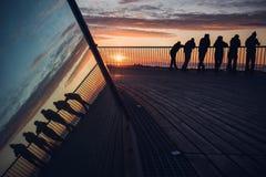 Silhouette des amis appréciant le coucher du soleil Photo stock
