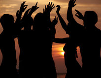 Silhouette des amis ayant la partie de plage Photo libre de droits