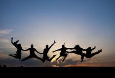 Silhouette des amis sautant dans le coucher du soleil Photos stock