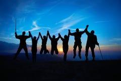 Silhouette des amis sautants Photographie stock