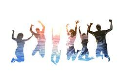 Silhouette des amis sautants avec le fond de la plage Images libres de droits