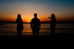 Silhouette des amis sur la plage Photo stock