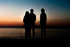 Silhouette des amis sur la plage Photographie stock libre de droits