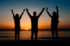 Silhouette des amis sur la plage Photos stock
