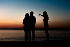 Silhouette des amis sur la plage Images libres de droits