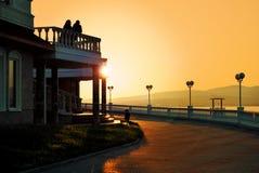 Silhouette des bâtiments non identifiés pendant le coucher du soleil de lever de soleil avec le ciel orangish dramatique de coule Photographie stock libre de droits