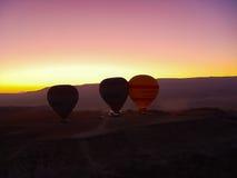 Silhouette des ballons à air chauds volant au-dessus de la vallée de Cappadocia Image libre de droits